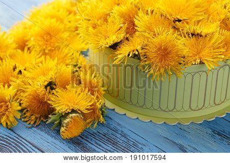 Box full of yellow flowers on wooden table