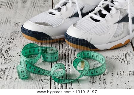 Sport Shoes And Measure Tape On White Background.sport Shoes And Centimeter As A Fitness Running