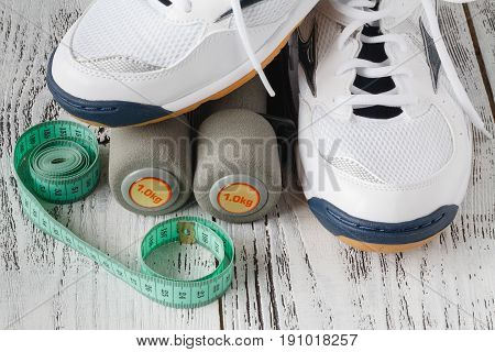 Sneakers And Pair Of Dumbbells On Wooden Background. Weights For A Fitness Training.