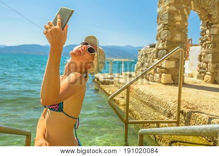 Summer outdoors. Happy tourist bikini vacation woman takes selfie at semi-enclosed natural swimming pool in Nafplio, Peloponnese, Greece, Europe. Woman with smart phone in travel holidays lifestyle.