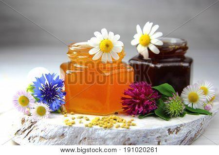 flower and buckwheat honey in jars with wildflowers