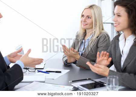 Group of business people applauding at meeting  in office.