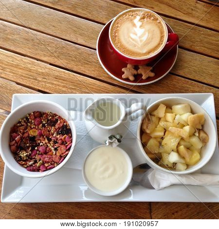 Muesli cereal granola with fresh kiwi fruit and flat white coffee for breakfast at cafe