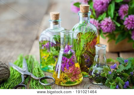 Bottles Of Tincture Or Infusion Of Healing Herbs, Scissors, Medicinal Herbs On Wooden Board. Herbal