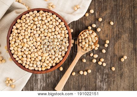 Soybeans in wooden cup on old wood background,top view