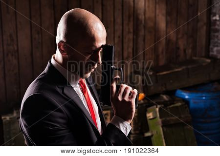 Contract assassin in suit and red tie holds gun