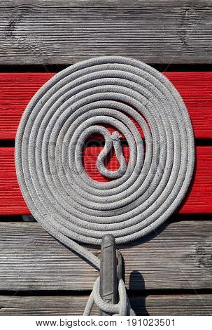 Sailing rope tied to a cleat on a pontoon with the excess rope coiled neatly on the pontoon with red painted wood. Space for text.