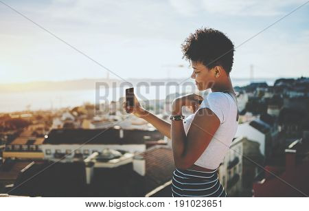 Beautiful and shy black girl is making selfie while standing on balcony in European city curly teenage afro american female is shooting Lisbon cityscape from high observation point on warm sunny day