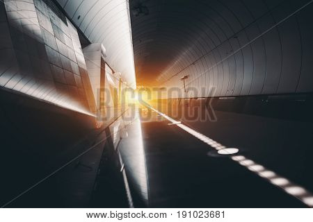 Futuristic view of subway hall with railway track illuminated restricting line vanishing point with flare multiple reflections; abstract contemporary long hall of marble metal lights and mirrors