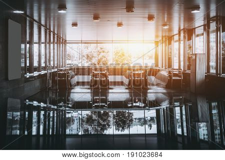Contemporary empty chrome and glass subway hall with several escalators and panoramic windows with strong reflection and frontal warm flare on sunny day
