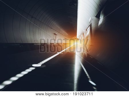 Abstract modern long hall interior with reflective walls and floor; contemporary empty subway station with platform and tunnel: illuminated white alert line with multiple lamps and reflections