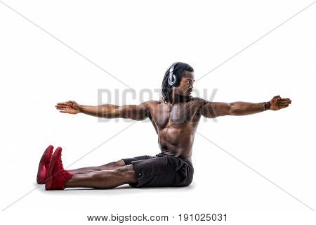 Handsome shirtless muscular black bodybuilder man exercizing while listening to music with headphones in studio shot isolated on white background. Full body shot