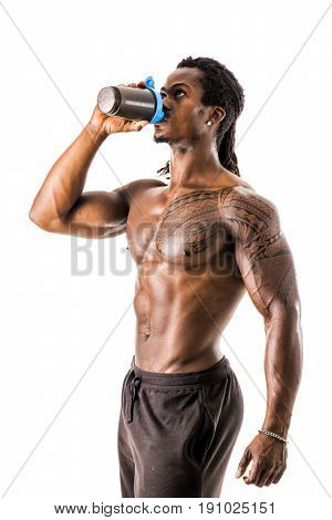 Muscular shirtless black male bodybuilder drinking protein shake from blender. Isolated on white, looking up