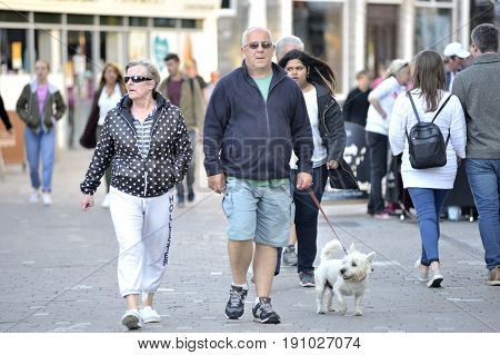 Shop Street Galway Ireland june 2017 Mature couple taking a walk with his dog.