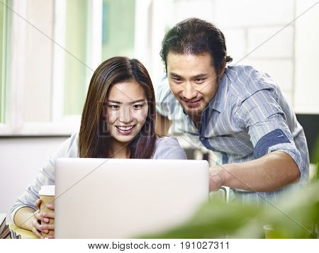 asian businessman and business woman working together in office using laptop computer.