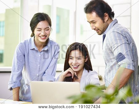 a team of young and cheerful asian business executives working together in office using laptop computer.