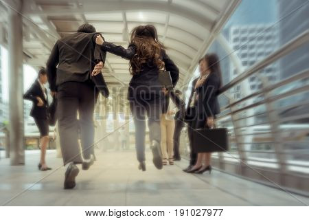 businessman and woman hurry up and running in business city street for rush hour motion blur background