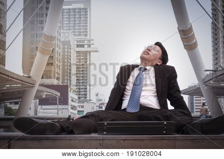Asian Businessman Wearing Glasses Tired And Briefcase For Working, Lay Down On The Floor
