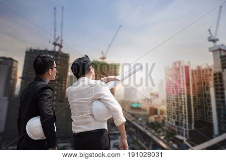 Asian Businessman Discuss With Engineer Architect Professional Wearing Safety Helmet And Suite, Look