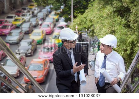 Asian Businessman Discuss With Engineer Architect Professional Wearing Safety Helmet And Holding Con