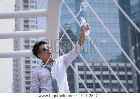 Asian Businessman Standing And Happy To Drink Water And Hold Bottle And Modern City Background