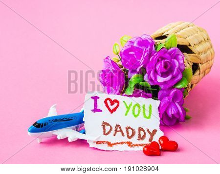 Father's day concept. I LOVE YOU DADY message with red rose two red heart airplane model and gift on pink background