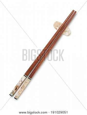 Top view of wooden chopsticks on chopstick rest isolated on white