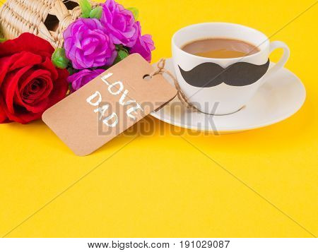 Father's day concept. Happy Father's Day and I LOVE DAD message on note book with pink flower coffee cup white gift and black Mustache on yellow background