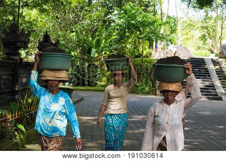 Women Carring Baskets On Their Heads At Tirta Empul Hindu Balinese Temple In Bali, Indonesia