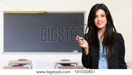 Smiling teacher in front of an empty blackboard