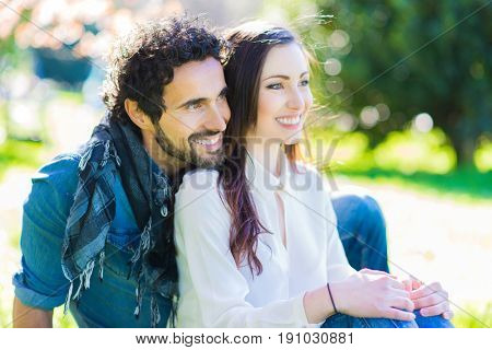 Young couple relaxing on the grass in the park
