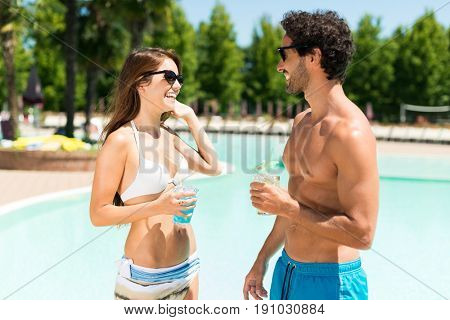 Young people talking in front of a pool