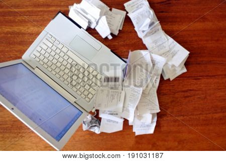 Above view of a laptop computer with receipts on a wooden table. Accountancy concept. copy space