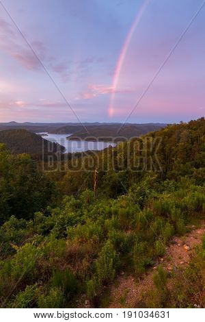 A rainbow in the sky during a beautiful sunset at Broken Bow Lake Oklahoma.