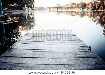 Empty wooden old berth on river on a calm, windless day