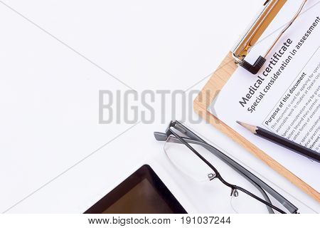 Workplace of a doctor. Medical certificate formglassespencil and smart phone on wooden desk background. Top view with copy space. Healty concept.