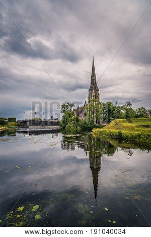 Church reflected on water pond in Churchill Park in Copenhagen a cloudy day of summer near sunset.