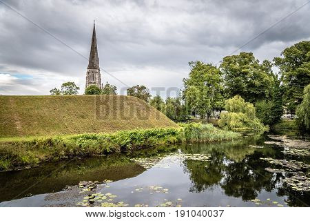 Water pond and church tower in Churchill Park in Copenhagen. It is a public park near Kastellet a 17th-century fortress.