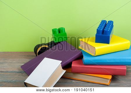 Open book, hardback colorful books, toy, shoes on wooden table. Back to school. Copy space for text. Education business concept