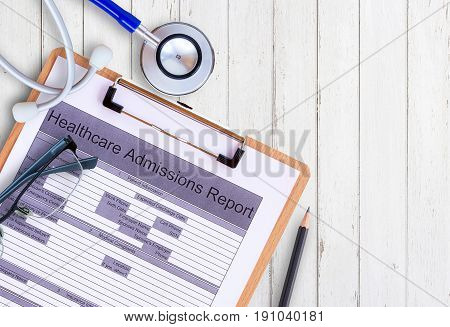 Workplace of a doctor. StethoscopeHealthcare Admission report formglassespencil on wooden desk background. Top view with copy space. Health concept.