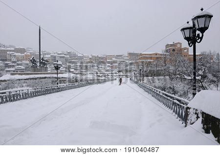 VELIKO TARNOVO BULGARIA - JANUARY 19 2017: Woman walks her dog along the snowy bridge near the monument of Assens on gloomy winter day