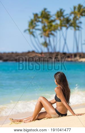 Hawaii tropical beach vacation tourist lady girl sitting down on sand relaxing enjoying sun. Summer travel tourism holiday people on holidays. Bikini woman tanning in summertime.
