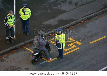 Traffic Police Officer Writing A Traffic Citation To A Scooter Rider