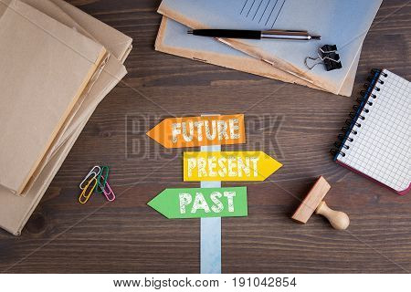 Future concept. Paper signpost on a wooden desk.