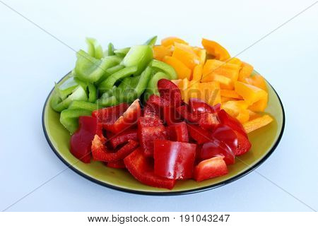 A plate filled with peppers in three fresh colors and cut into squares