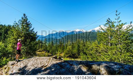 Woman looking at the Tantalus Mountain Range with snow covered peaks of Alpha Mountain, Serratus and Tantalus Mountain, seen from a viewpoint along the Sea to Sky Highway between Squamish and Whistler