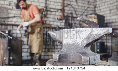 A muscular young man working with a circular saw, in the forge, slider