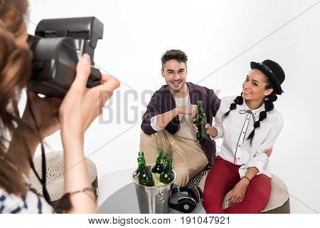 Cropped Shot Of Woman With Instant Camera Photographing Happy Young Couple Drinking Beer Together