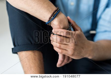 Close-up partial view of young man with wooden bracelets on hand sitting on grey