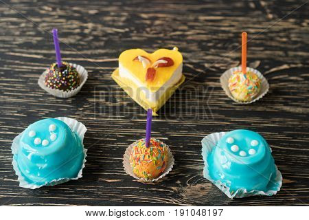 Delicious colourful cup cakes on wooden background.